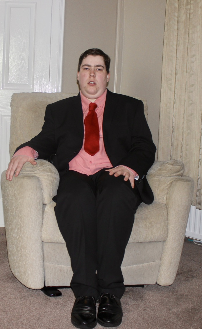A full body picture of myself, wearing a black suit, sat on a grey chair, with a grey and white background.