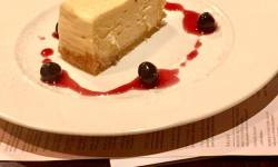 A creamy white wedge of cheesecake, with a tan base, and some red sauce circling the plate, with some red cherries, on a white plate, on a brown and white background.