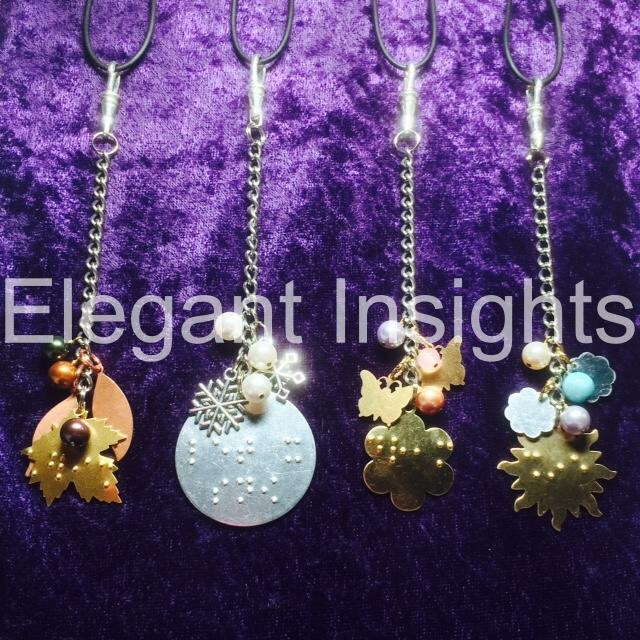 A tan brown maple leaf charm, - silver disco ball shaped charm, a brightly coloured sun charm and a light green butterfly charm all on silver linked chains on a sparkly purple background.
