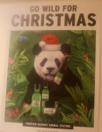 A White poster, with a picture of a panda wearing a santas hat, and holding some of The Body Shop's Christmas products, on a green background, with some green text saying Go Wild About Christmas on it, on a white background.