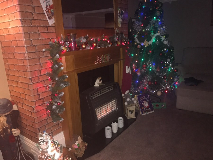 A dark green Christmas tree covered in some blue lights next to a dark brown fireplace and a light brown mantle piece covered in some red lights, on a white background.