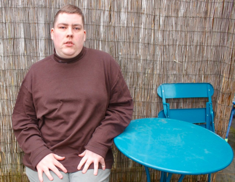 A person wearing a chocolate brown roll neck top, sat down on a blue chair next to a blue table, on a light wood background.