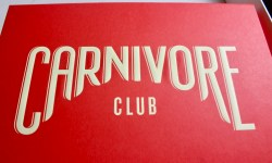 A large bright red rectangular Cardboard box that has Carnivore written in large white capital letters, and club written in smaller white capital letters on it, on a white background.
