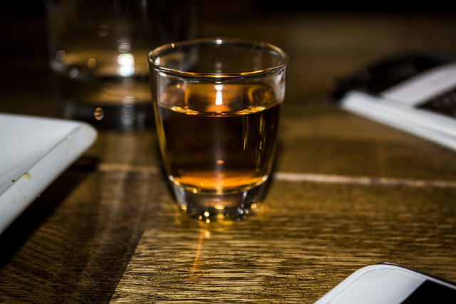 Some dark amber liquid in a small cylindrical shot glass on a wooden table surrounded by white rectangular napkins, on a dark background.