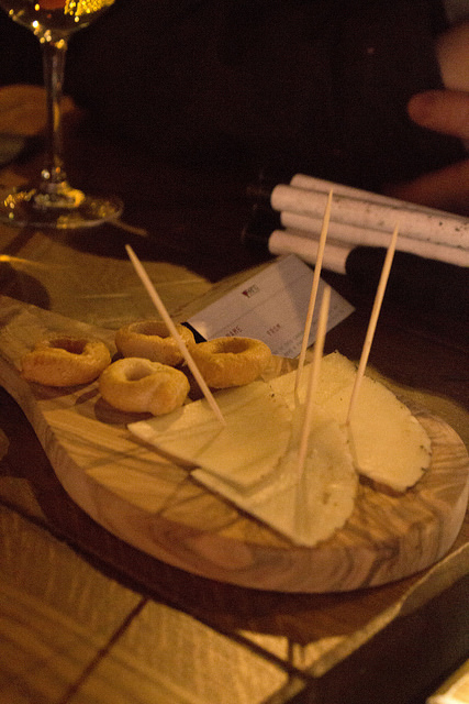 Some Square pieces of light yellow Cheese on some tan thin cocktail sticks next to some cubes of light tan bread with holes in the middle of them on a wooden board, on a dark background.