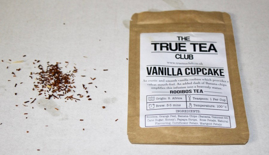 A rectangular brown pouch with a white label that has True Tea Club Vanilla Cupcake Rooibos Loose Leafed Tea written in black writing on it, with some black Tea Leaves next to the pouch, on a white background.