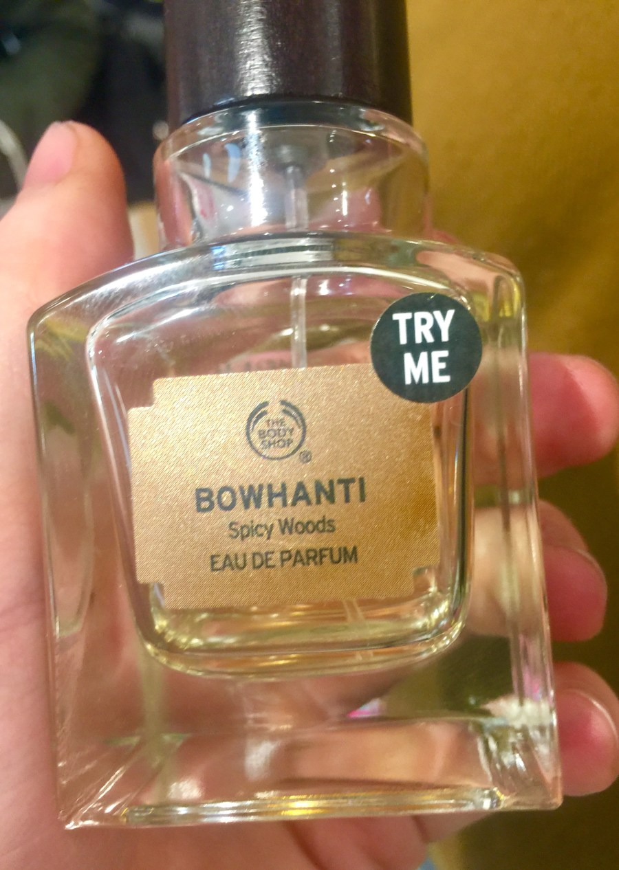 A square glass bottle filled with some clear liquid with a gold label that has the body shop bowhanti written on it in black writing, on a bright background.