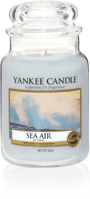 A tall glass jar full of light blue coloured wax, with a label that has a picture of some fog above the Sea, and Yankee Candle and Sea Air written in black writing on it, on a white background.