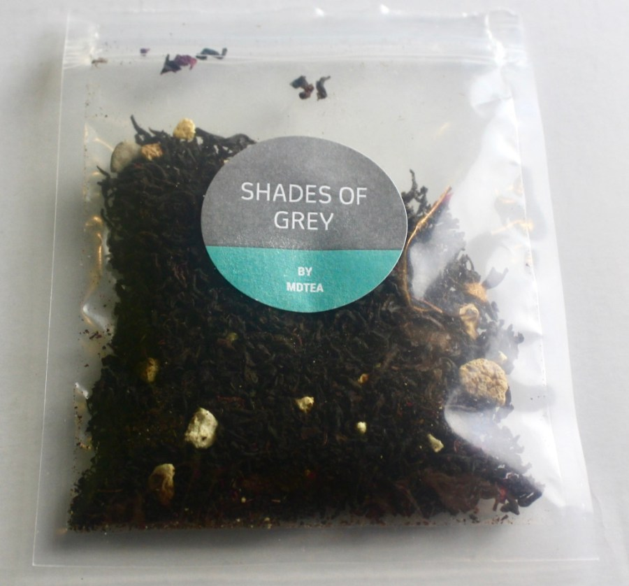 A square clear plastic bag containing some dark green tea leaves with a grey circular sticker that has Shades Of Grey written in medium white writing and MDTea written in smaller white writing on it, on a white background.