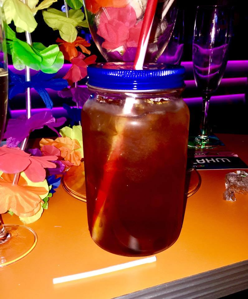 A clear mason jar with a blue screw top lid full of some red coloured liquid and a bright yellow straw, with some brightly coloured flowers in the background, on a dark background.