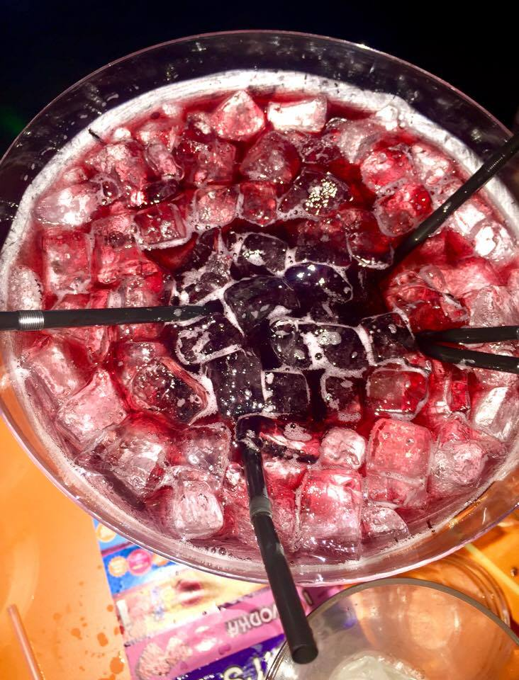 A large Martini glass full of some deep purple liquid, some clear ice cubes and some black straws, on a light wooden table, on a dark background.