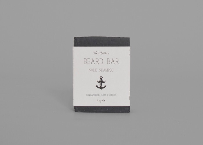 A rectangular black box covered with a white slip that has Brighton beard company beard bar written in black writing and a black anchor logo next to it, on a grey background.