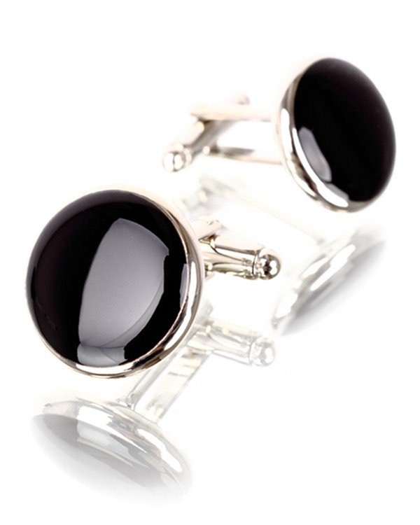 Two big black onyx circular cufflinks with metal ends that tie into the cuffs, on a white background