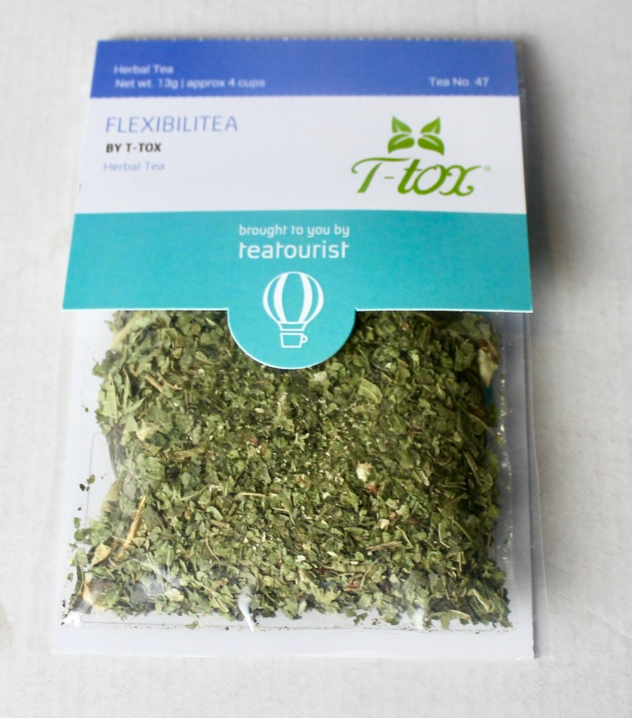 A square clear plastic bag containing some dark brown tea leaves with a cardboard label that has Flexibilitea written in light blue writing and Teatox written in smaller light green writing on it, on a white background.