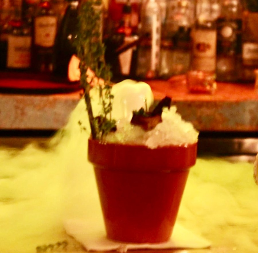A large light wooden plant pot filled with some clear ice cubes, some black straws, and a cocktail hidden beneath some dry ice on a light wooden bar, on a dark background.