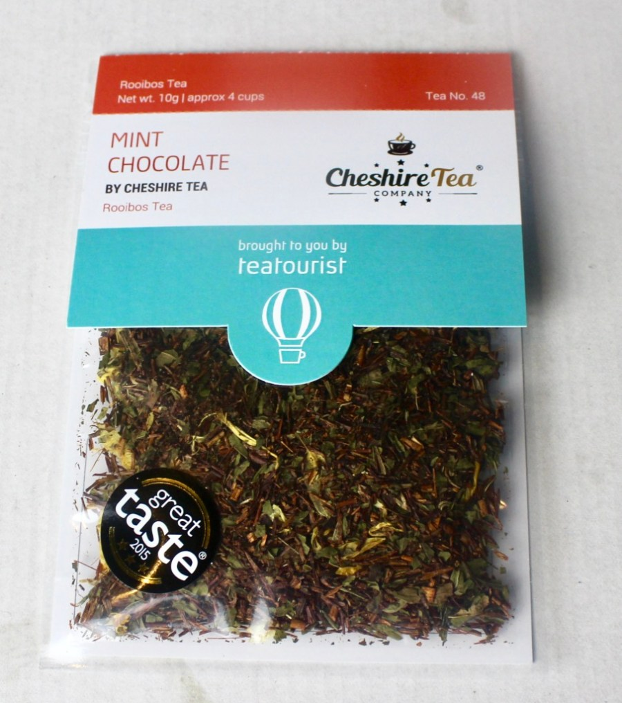 A square clear plastic bag containing some dark brown tea leaves with a cardboard label that has Mint Chocolate written in light red writing and Cheshire Tea written in smaller dark brown writing on it, on a white background.