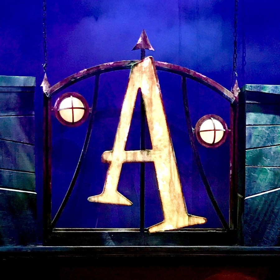 A large gold coloured Letter A, two circular lights, and an arch on a black platform, on a blue background.