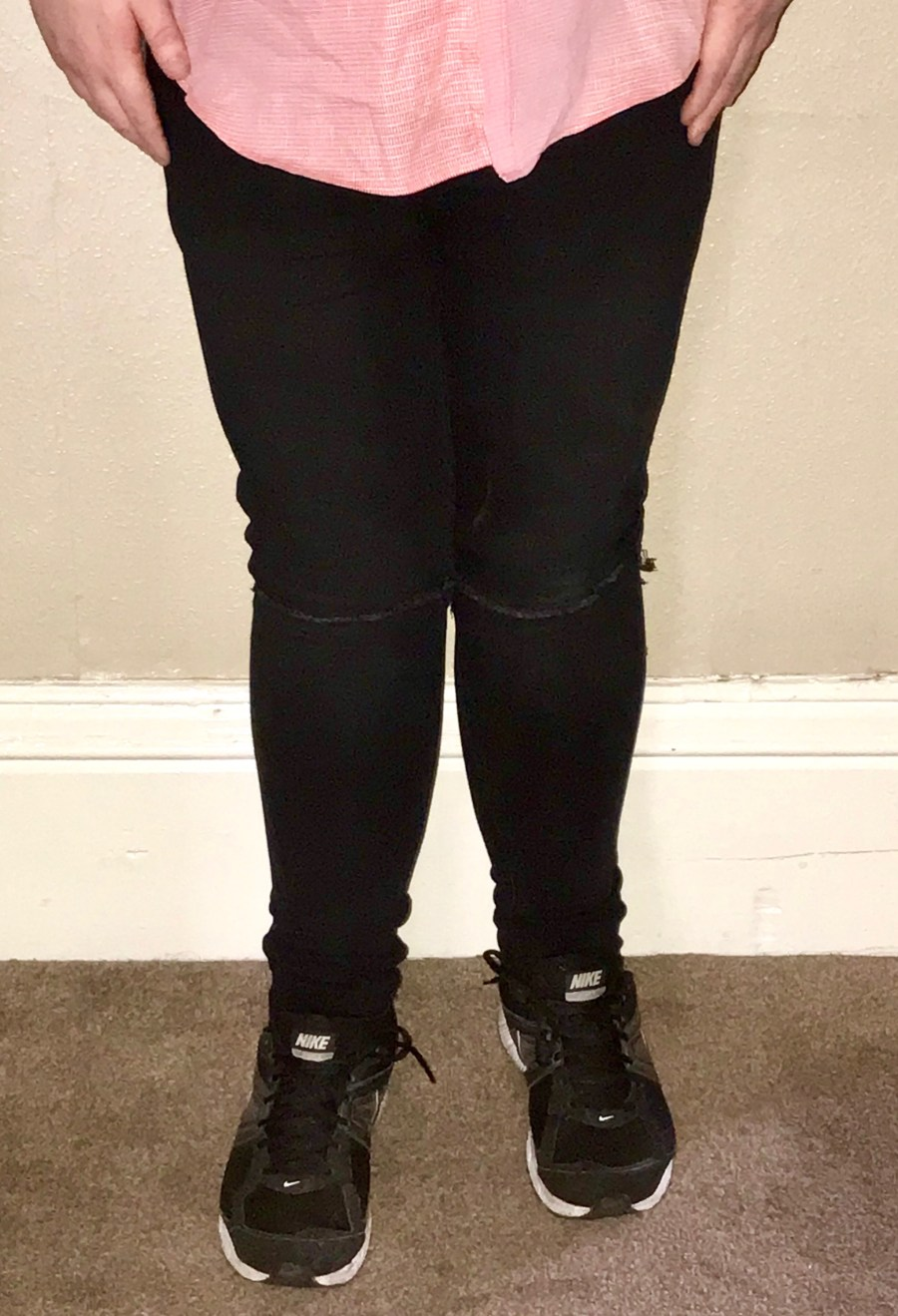 Me wearing a pair of Black skinny fit knee ripped jeans and a pair of black trainers with white soles on a brown carpet, on a light green background.