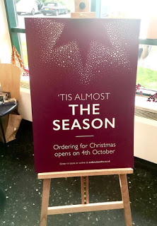 A dark Red Glittery advertisement board on a light wooden cardboard easel that has 'tis nearly written in small Gold writing and the season written in big bold white writing on it, on a nighttime background.