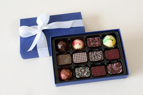 A large rectangular landscape box full of some circular and rectangular black and white chocolates next to a Purple box lid and a large white tied ribbon, on a white background.