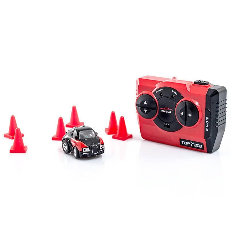 A small Red 4X4 Car with some Black Tyres and White Head Lights next to some bright Orange cones and a large Black and Red remote control, on a white background.