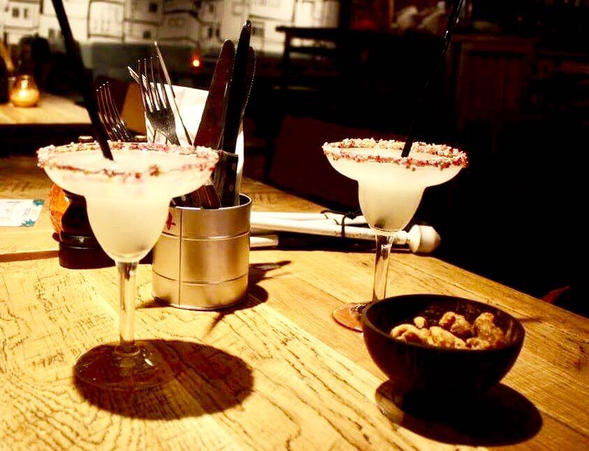 Two tall clear glasses with multi-coloured sprinkles covered rims full of some thick white liquid next to a light brown bowl full of some golden pork scratchings on a light wooden table, on a light background.