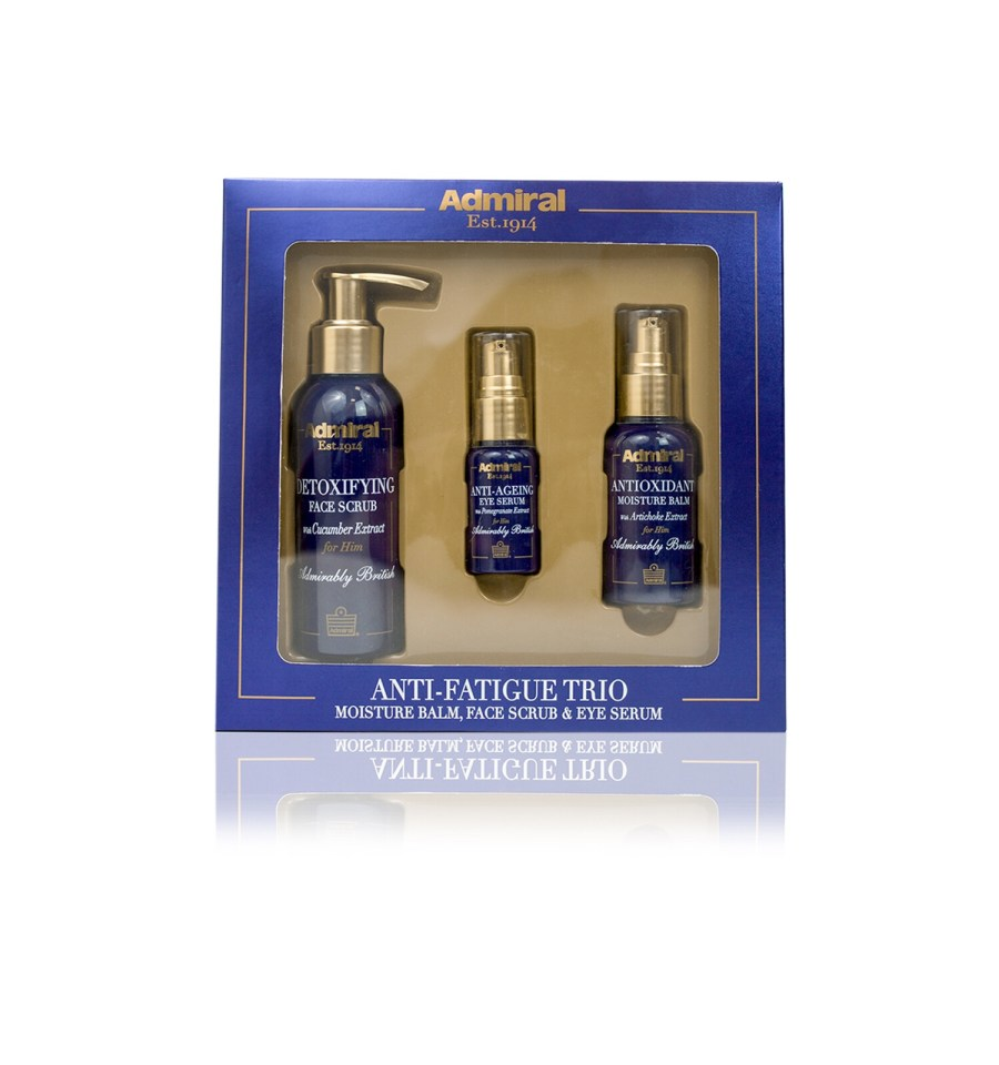 Three different sized cylindrical black bottles with gold lids and pumps sat on a light brown cardboard tray inside a rectangular blue box that has admiral grooming Anti-Fatigue Trio written in bold gold writing, and antioxidant moisture balm, detoxifying facial scrub, and anti-ageing eye serum written in smaller gold writing on it, on a white background.