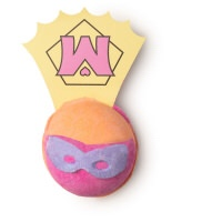 A light yellow spherical shaped bath bomb that has a bright pink crescent and a pair of purple glasses engraved into it and a white piece of paper that has a yellow triangle and a pink M on it attached to the back of it, on a white background.