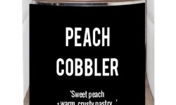 A silver metal cylindrical tin that has a black rectangular label, Peach Cobbler written in large bold white writing, and with sweet Peach and warm crusty pastry and bluebirdteaco.com written in smaller white writing on it, on a white background.