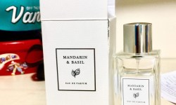 A tall rectangular white Cardboard box that has Mandarin & Basil Eau De Parfum written in bold black writing inside a white square with a gold border on it, next to a tall rectangular glass bottle with a silver cylindrical lid that has mandarin & Basil Eau De Parfum written in bold black writing inside a clear square with a gold border on it, on a white background.