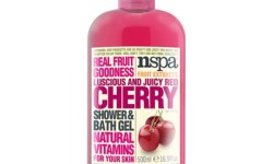 A tall cylindrical plastic bottle full of some dark pink liquid with a white label that has NSPA written in bold black writing, cherry Shower & Bath Gel written in bold red writing, and a picture of a Cherry on it, on a white background.