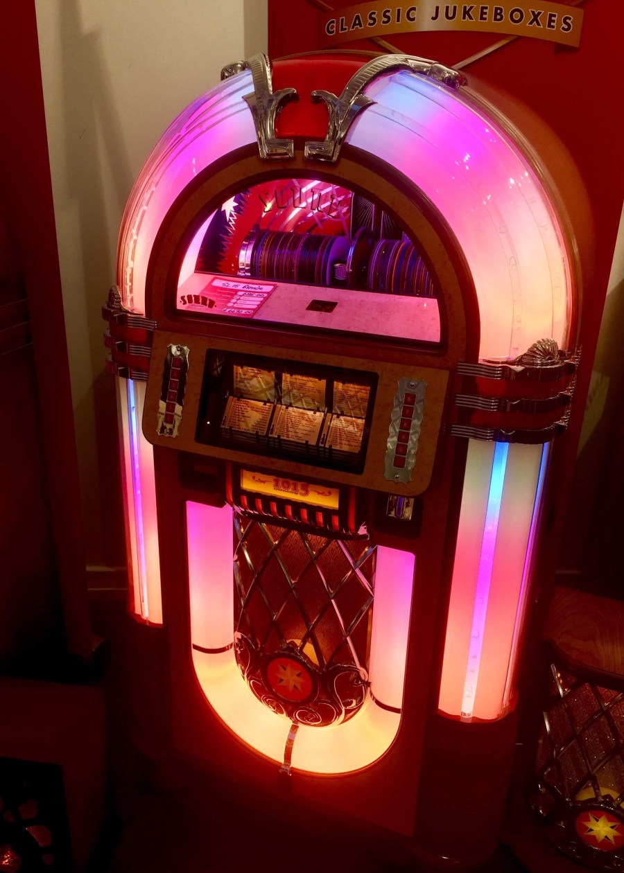 An arch shaped clear glass and dark brown wooden Jukebox that has a semi circled clear glass screen, some white plastic square buttons, and some yellow, pink and purple lights on it, on a dark background.