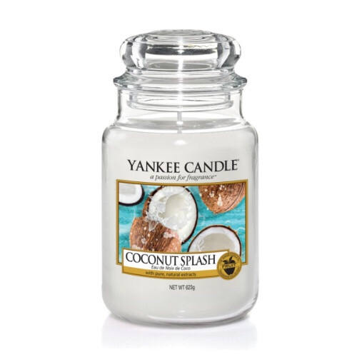 A tall glass jar full of some white coloured wax with a label that has yankee candle written in black writing, Coconut Splash written in black writing, and a picture of some grey coconut shells with creamy white insides next to some green spiky leaves on it, on a bright background.