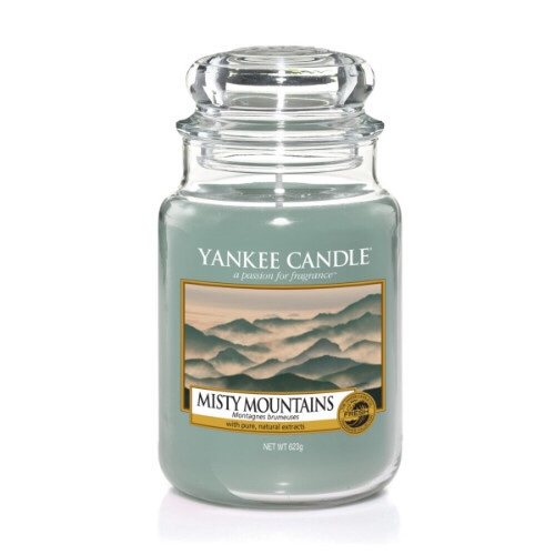 A tall glass jar full of some Ice Blue coloured wax with a label that has yankee candle written in black writing,Misty Mountains written in black writing, and a picture of a bright ice blue sky behind some ice white snow topped mountains on it, on a bright background.