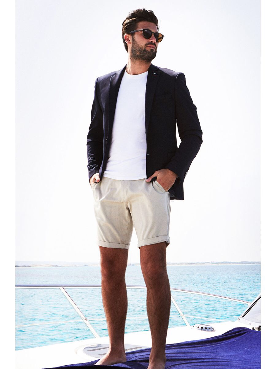 A man stood on a boat with the Sea in the distance wearing a pair of Beige Chino Shorts, a plain White T-Shirt, a navy blue blazer and a pair of dark Sunglasses, on a white background.