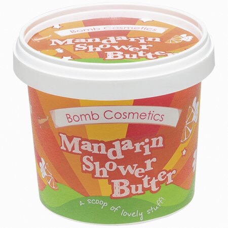 A short cylindrical Orange and Yellow plastic tub that has Bomb Cosmetics Mandarin Cleansing Shower Butter written in white writing on it, on a white background.