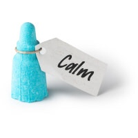 A sky blue miniature bottle shaped bath bomb with a paper label that has Calm written in bold black writing on it, on a white background.
