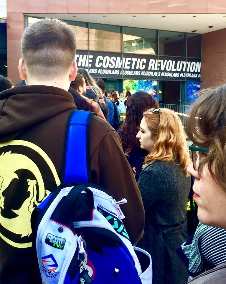 A long queue of several people including a person wearing a Blue Coat and a Black Backpack in front of a bright Blue banner that has welcome to the cosmetic revolution written in bold white writing on it, on a bright background.