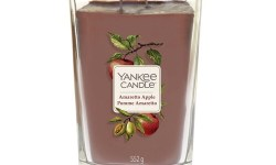A tall rectangular clear glass jar with a square gold lid full of some purple wax with a label that has Yankee Candle Amaretto Apple written in bold black writing and a picture of some green apples on it, on a white background.
