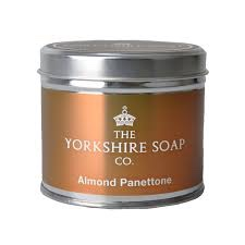 A tall Silver Metal Tin with a white label that has The Yorkshire Soap Company Almond Panettone Tin Candle written in bold black writing on it, on a white background.
