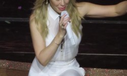 A short woman with blond hair wearing a white jumpsuit and holding a white microphone kneeling on one knee on a dark wooden stage, on a white background.