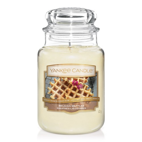 A tall glass jar full of some bright white wax with a label that has Yankee Candle written in gold writing, belgian waffles written in white writing, and a picture of a belgian waffle on it, on a white background.