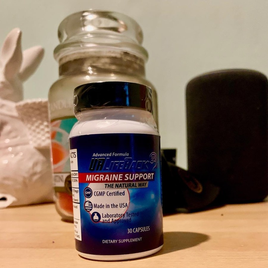 A short cylindrical white plastic bottle with a blue label that has URLifeBack Migraine & Headache Support Supplements written in bold white writing on it, on a white background.
