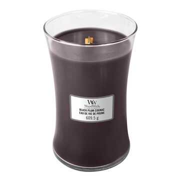 A tall hourglass shaped glass jar full of some dark purple wax with a white label that has WoodWick Candles written in gold writing and Black Plum Cognac written in black writing on it, on a white background.