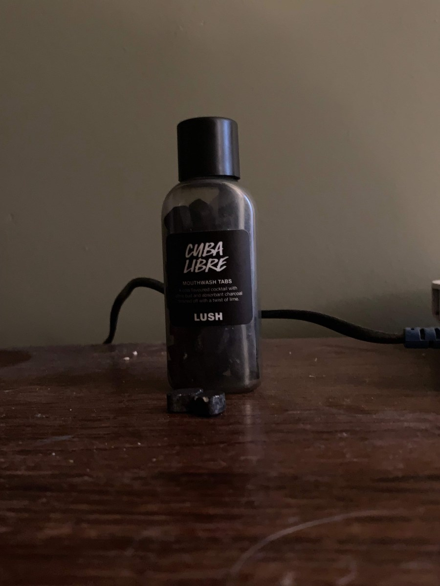 A short and flat rounded rectangular clear plastic bottle with a black lid and a black label that has Lush Cuba Libre Mouthwash Tabs written in bold white writing on it next to some small black diamond shaped pieces of powder, on a white background.