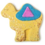 A large flat dark brown Camel shaped bath bomb that has a bright blue Saddle and two golden star shaped eyes on it, on a white background.