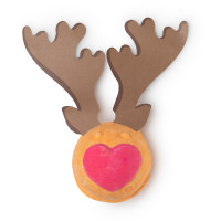 A small dark brown bath bomb that has a bright red nose on it and a pair of paper antlers sticking out of the top of it, on a white background.