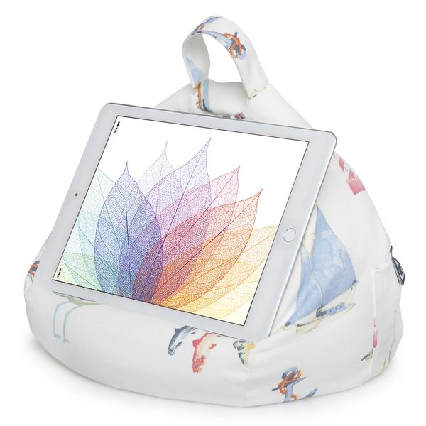 A large circular white cushion that has some pictures of some different coloured boats, anchors and fish on it, on a white background.