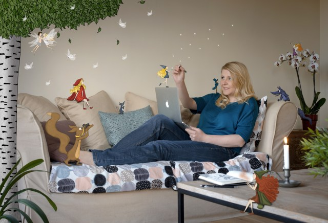 Auto-portrait de Lumi Poullaouec sur son canapé dessinant le monde féérique qui l'entoure.