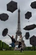 Photomontage. Deux jeunes filles blondes et heureuses sautent devant la tour Eiffle. Tout autour d'elles des parapluies noirs. ©Lumi Poullaouec